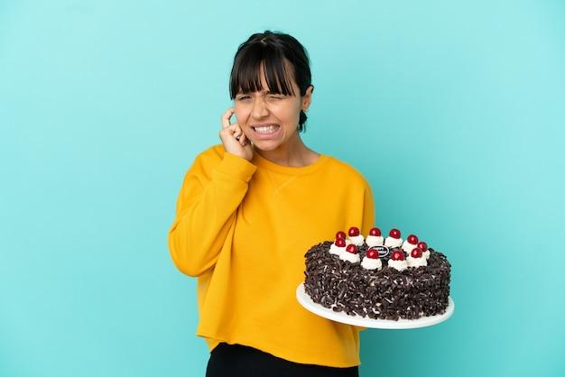 Молодая женщина смешанной расы, держащая праздничный торт разочарована и закрывающая уши