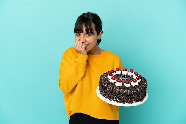バースデーケーキを幸せに保持し、手で口を覆って笑顔の若い混血の女性