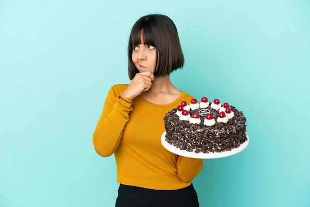 Молодая женщина смешанной расы держит торт ко дню рождения, сомневаясь и с смущенным выражением лица