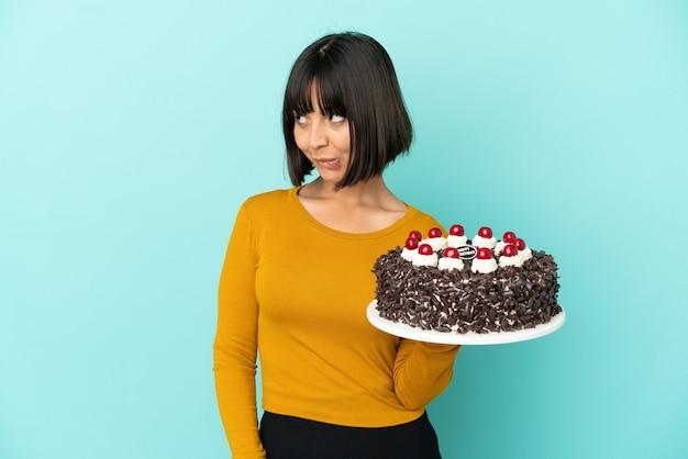 Молодая женщина смешанной расы держит торт ко дню рождения, сомневаясь, глядя вверх