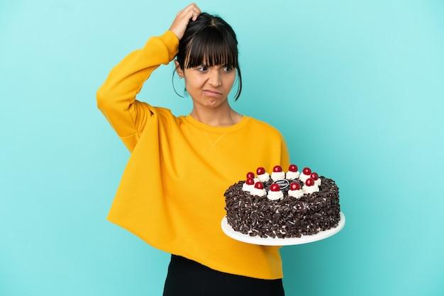 Молодая женщина смешанной расы держит торт ко дню рождения, сомневаясь, почесывая голову