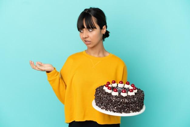 Молодая женщина смешанной расы держит торт ко дню рождения, держа copyspace с сомнениями
