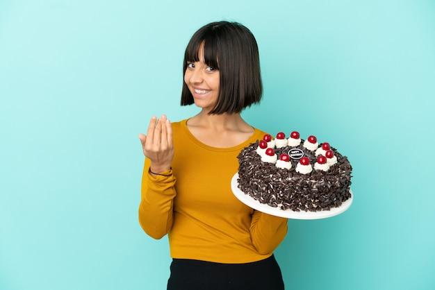 Молодая женщина смешанной расы, держащая торт ко дню рождения, приглашая прийти с рукой. счастлив что ты пришел