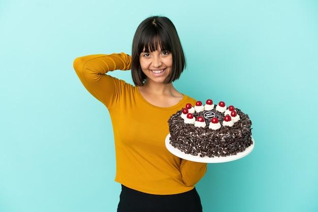 Молодая женщина смешанной расы, держащая торт ко дню рождения смеясь