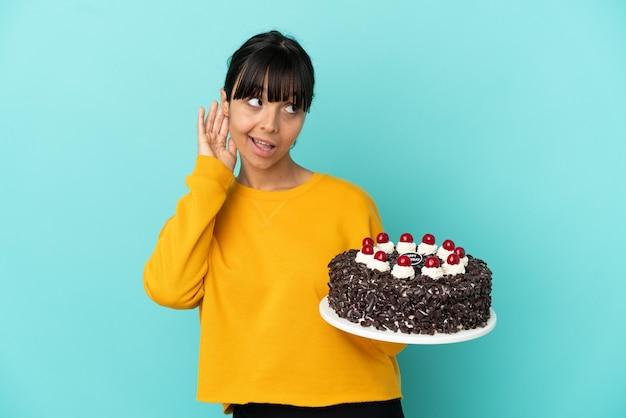 Молодая женщина смешанной расы держит торт ко дню рождения, слушая что-то, положив руку на ухо