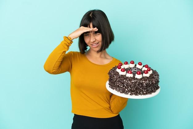 Молодая женщина смешанной расы, держащая торт ко дню рождения, смотрит вдаль рукой, чтобы что-то посмотреть