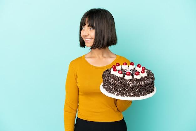 Молодая женщина смешанной расы держит торт ко дню рождения