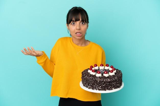 Молодая женщина смешанной расы держит торт ко дню рождения, делая жест сомнения