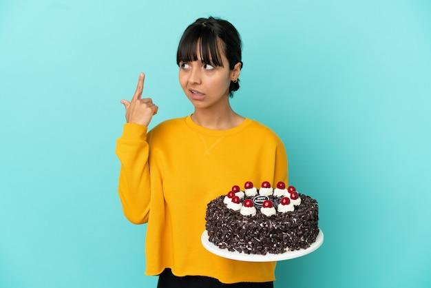 Молодая женщина смешанной расы держит торт ко дню рождения, делая жест безумия, положив палец на голову