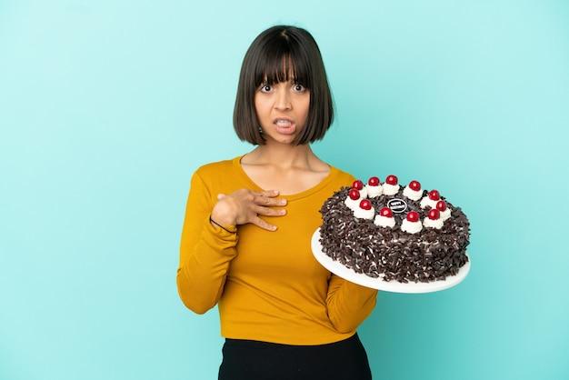 Молодая женщина смешанной расы держит торт ко дню рождения, указывая на себя