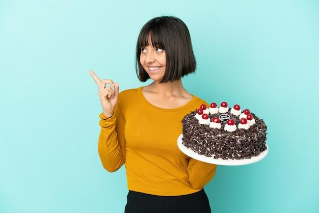 Молодая женщина смешанной расы держит торт ко дню рождения, указывая вверх отличную идею