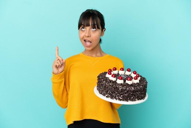 上向きと驚いたバースデーケーキを保持している若い混血の女性