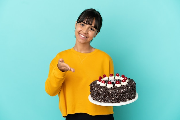 Молодая женщина смешанной расы держит торт ко дню рождения, пожимая руку для заключения хорошей сделки