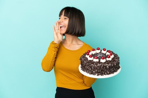 Молодая женщина смешанной расы, держащая торт ко дню рождения, кричит с широко открытым ртом в сторону