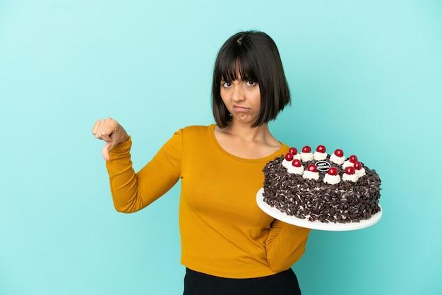Молодая женщина смешанной расы держит торт ко дню рождения, показывая большой палец вниз с отрицательным выражением лица