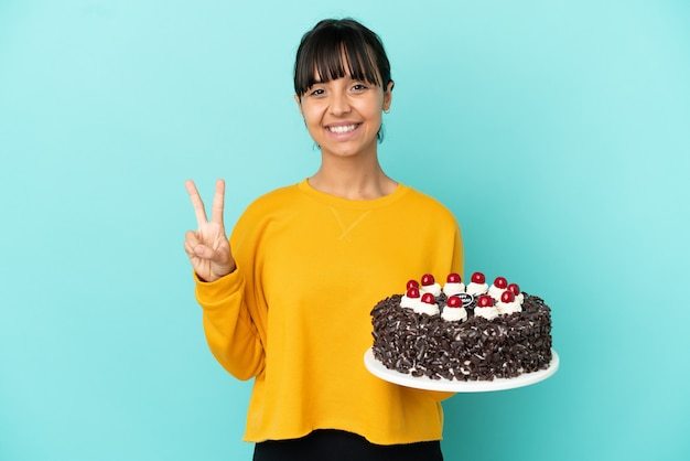 Молодая женщина смешанной расы, держащая торт ко дню рождения, улыбается и показывает знак победы