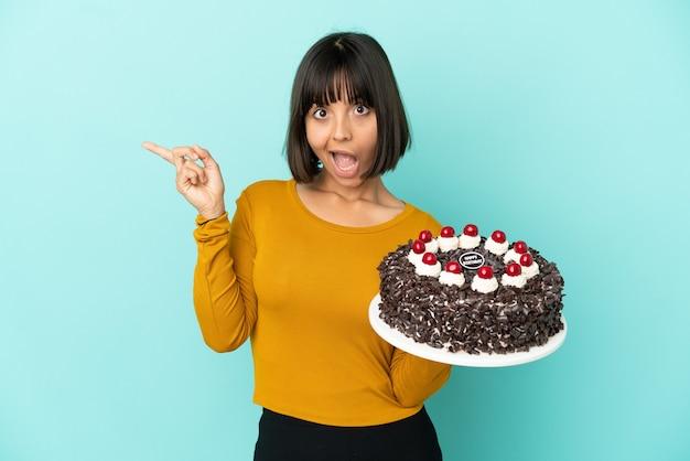 Молодая женщина смешанной расы, держащая торт ко дню рождения, удивлена и показывает пальцем в сторону