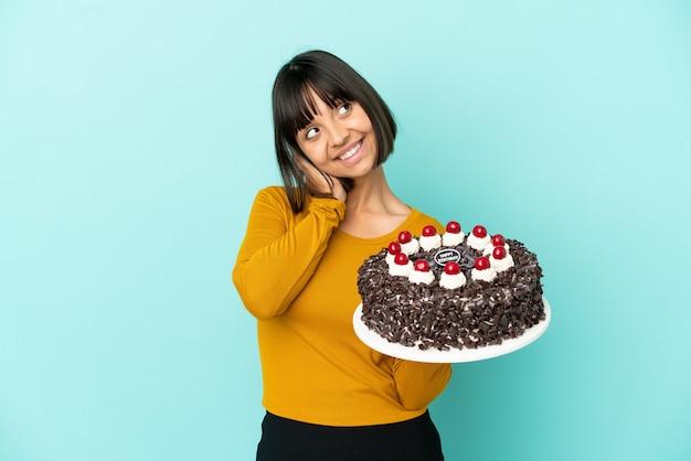 Молодая женщина смешанной расы держит торт ко дню рождения, думая об идее