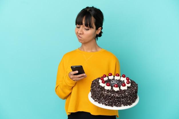 Молодая женщина смешанной расы держит торт ко дню рождения, думая и отправляя сообщение