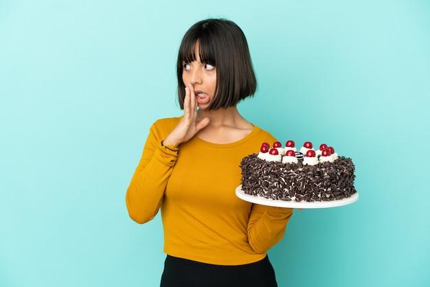 Молодая женщина смешанной расы, держащая торт ко дню рождения, шепчет что-то с удивленным жестом, глядя в сторону