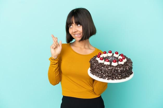 Молодая женщина смешанной расы держит праздничный торт со скрещенными пальцами и желает всего наилучшего