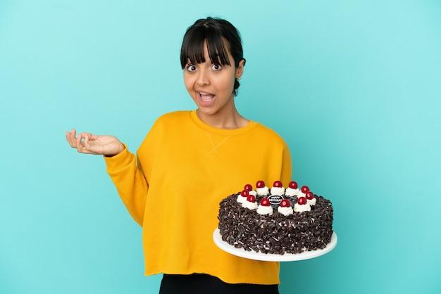 Молодая женщина смешанной расы держит праздничный торт с шокированным выражением лица