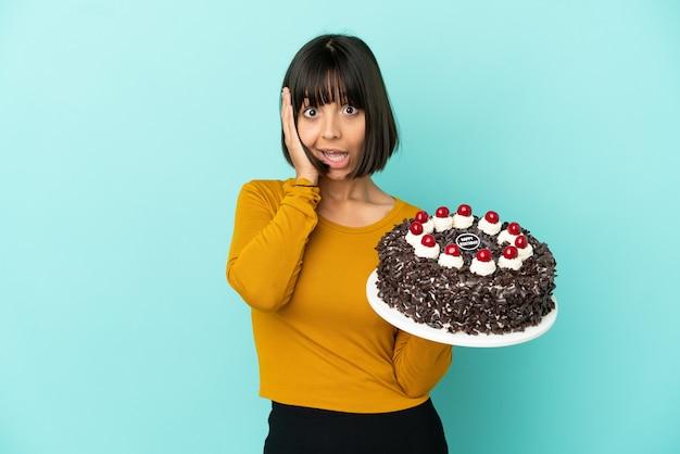 Молодая женщина смешанной расы держит праздничный торт с удивленным выражением лица