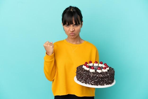 Молодая женщина смешанной расы держит торт ко дню рождения с несчастным выражением лица