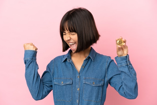 Young mixed race woman holding a bitcoin isolated background celebrating a victory