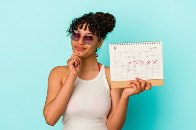 Young mixed race woman holding calendar isolated on blue background looking sideways with doubtful and skeptical expression.