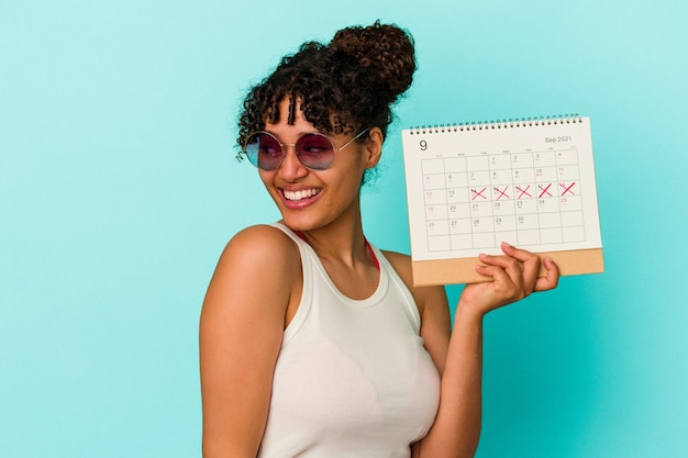 Young mixed race woman holding calendar isolated on blue background looks aside smiling, cheerful and pleasant.