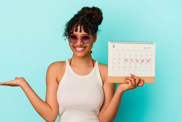 Young mixed race woman holding calendar isolated on blue background showing a copy space on a palm and holding another hand on waist.
