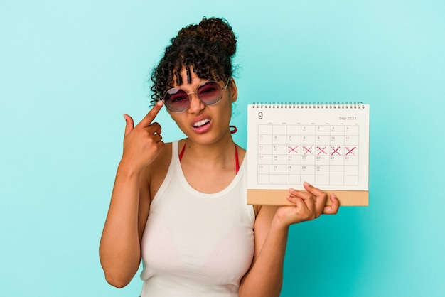 Young mixed race woman holding calendar isolated on blue background showing a disappointment gesture with forefinger.