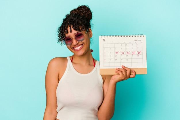 Молодая женщина смешанной расы, держащая календарь, изолированные на синем фоне, счастливая, улыбающаяся и веселая.