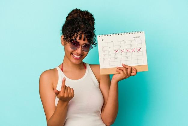 Молодая женщина смешанной расы, держащая календарь, изолирована на синем фоне, указывая пальцем на вас, как будто приглашая подойти ближе.
