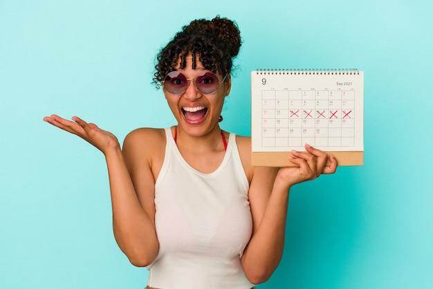 青の背景にカレンダーを保持している若い混血の女性が、うれしい驚きを受け、興奮し、手を上げている。