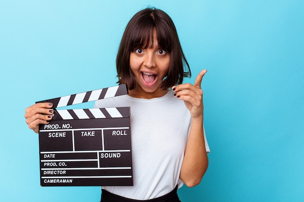 Young mixed race woman holding a clapper board having an idea, inspiration concept.