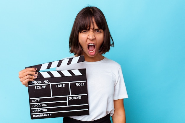 Young mixed race woman holding a clapper board screaming very angry and aggressive.
