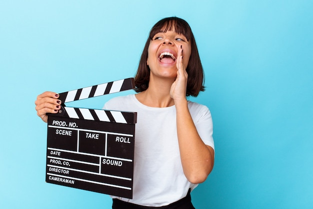 Young mixed race woman holding a clapper board shouting and holding palm near opened mouth.