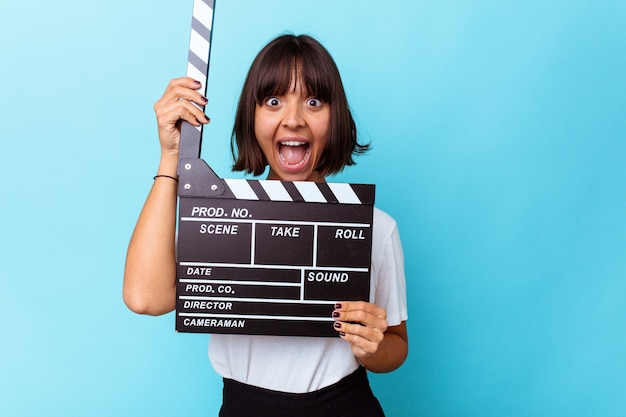 Young mixed race woman holding a clapper board