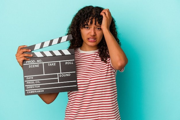 Young mixed race woman holding a clapperboard isolated on blue background being shocked, she has remembered important meeting.