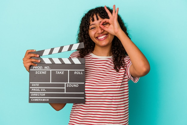 Young mixed race woman holding a clapperboard isolated on blue background excited keeping ok gesture on eye.