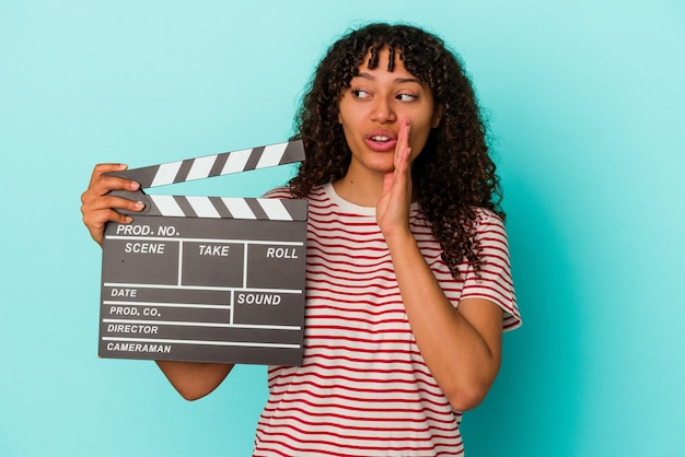 Young mixed race woman holding a clapperboard isolated on blue background is saying a secret hot braking news and looking aside