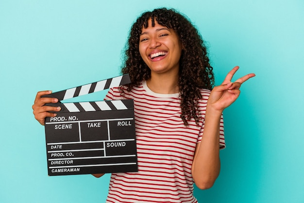 Young mixed race woman holding a clapperboard isolated on blue background joyful and carefree showing a peace symbol with fingers.