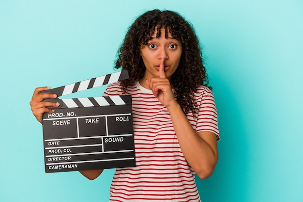 Young mixed race woman holding a clapperboard isolated on blue background keeping a secret or asking for silence.