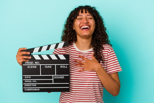 Young mixed race woman holding a clapperboard isolated on blue background laughs out loudly keeping hand on chest.