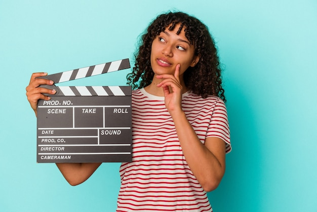 Young mixed race woman holding a clapperboard isolated on blue background looking sideways with doubtful and skeptical expression.