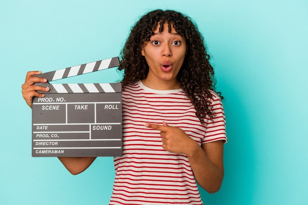 Young mixed race woman holding a clapperboard isolated on blue background pointing to the side