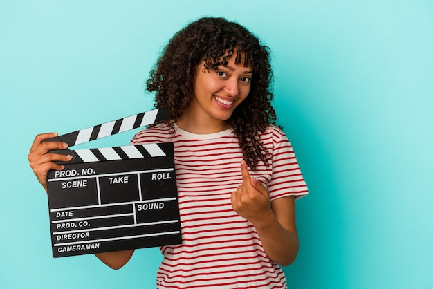 Young mixed race woman holding a clapperboard isolated on blue background pointing with finger at you as if inviting come closer.