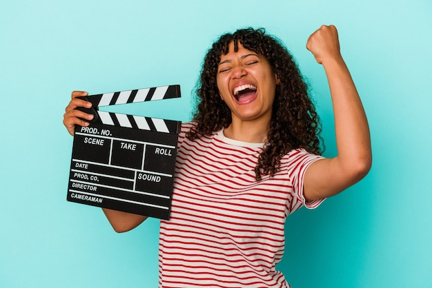 Young mixed race woman holding a clapperboard isolated on blue background raising fist after a victory, winner concept.